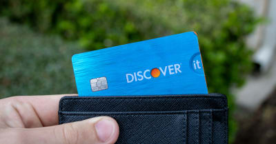 A hand and wallet holds a Discover It Student Miles credit card