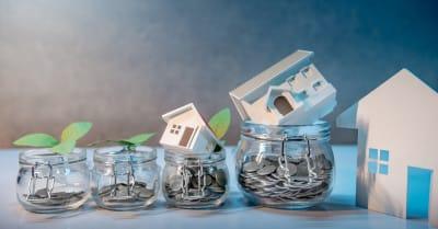 Ahorrar dinero para la jubilación.Inversión inmobiliaria. Tipo de préstamo hipotecario. Monedas, billetes en dólares, tarjeta de crédito y modelo de casa en tarros de vidrio sobre la mesa. Concepto de crecimiento financiero