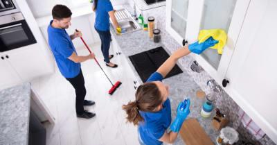 Grupo De Jóvenes Jinetes En Cocina De Limpieza Uniforme En Casa