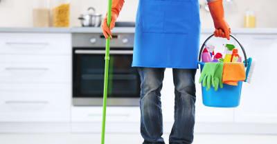 Hombre sujeta cucharas de plástico con cepillos, guantes y detergentes en la cocina
