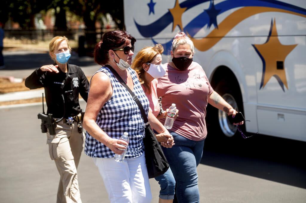 Varias mujeres son retiradas de un espacio para reuniones de trabajadores de la Autoridad de Transporte del Valle de Santa Clara el miércoles 26 de mayo de 2021 después de que un sujeto matara a tiros a varias personas en la terminal ferroviaria de la agencia en San José, California.