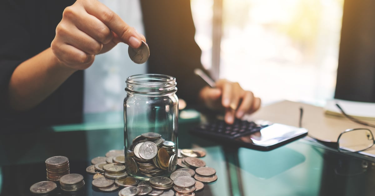 Imagen de un empresario apilando y poniendo monedas en un frasco de vidrio