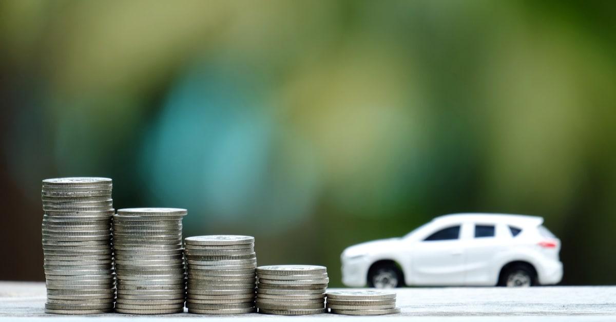 Unas monedas con un automóvil en el fondo
