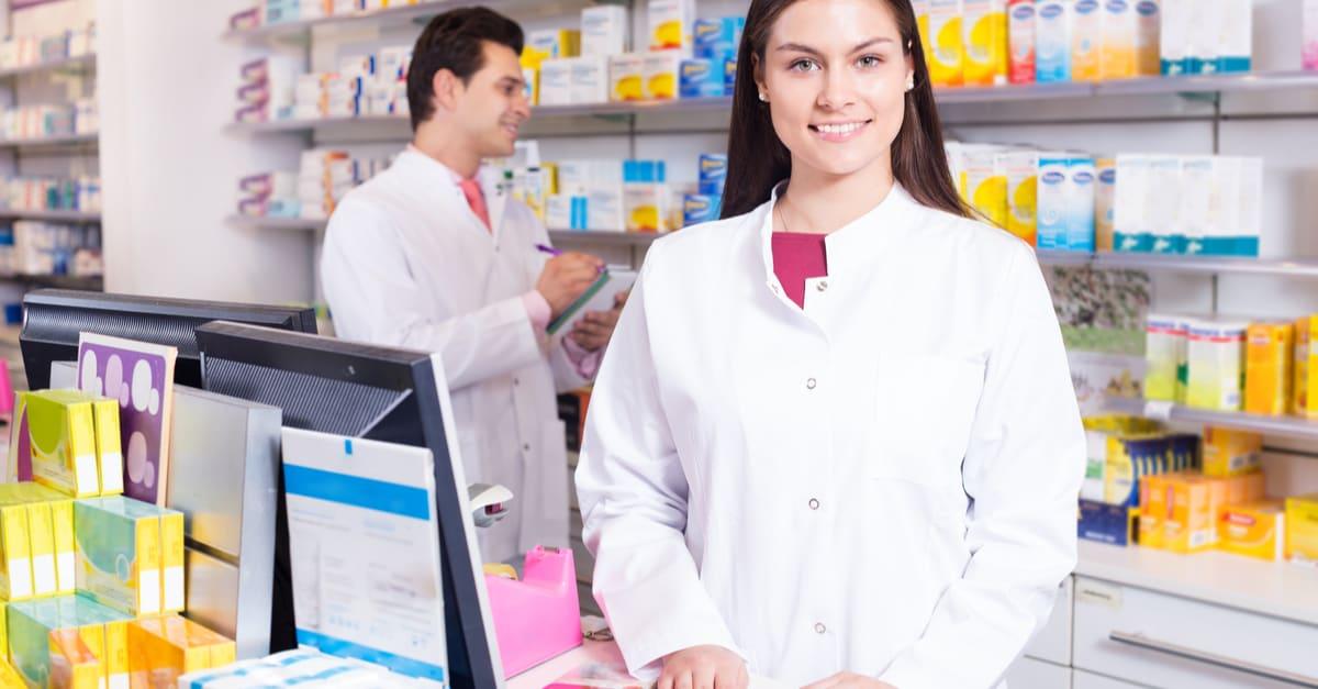 Unos empleados de una farmacia sonriendo y viendo medicamentos