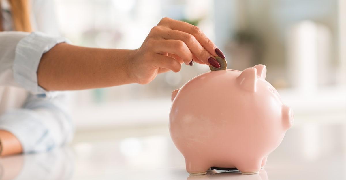 Cochinito recibiendo monedas como concepto de ahorro por descuentos