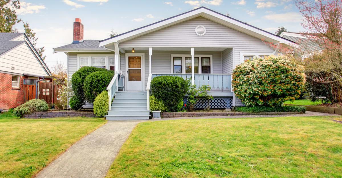 Casa de fachada beige con porche cubierto y arbustos recortados en frente madera