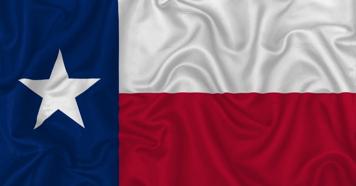 bandera de estado texas en un fondo de textura satinada de tela de seda ondulada.