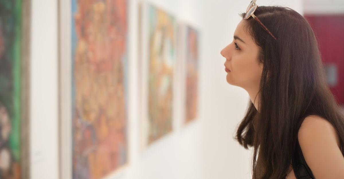 Una mujer latina viendo cuadros hechos por inmigrantes