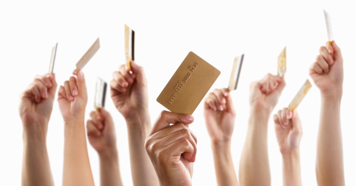 Muchas manos levantando y manteniendo una tarjeta de crédito de oro, con fondo blanco