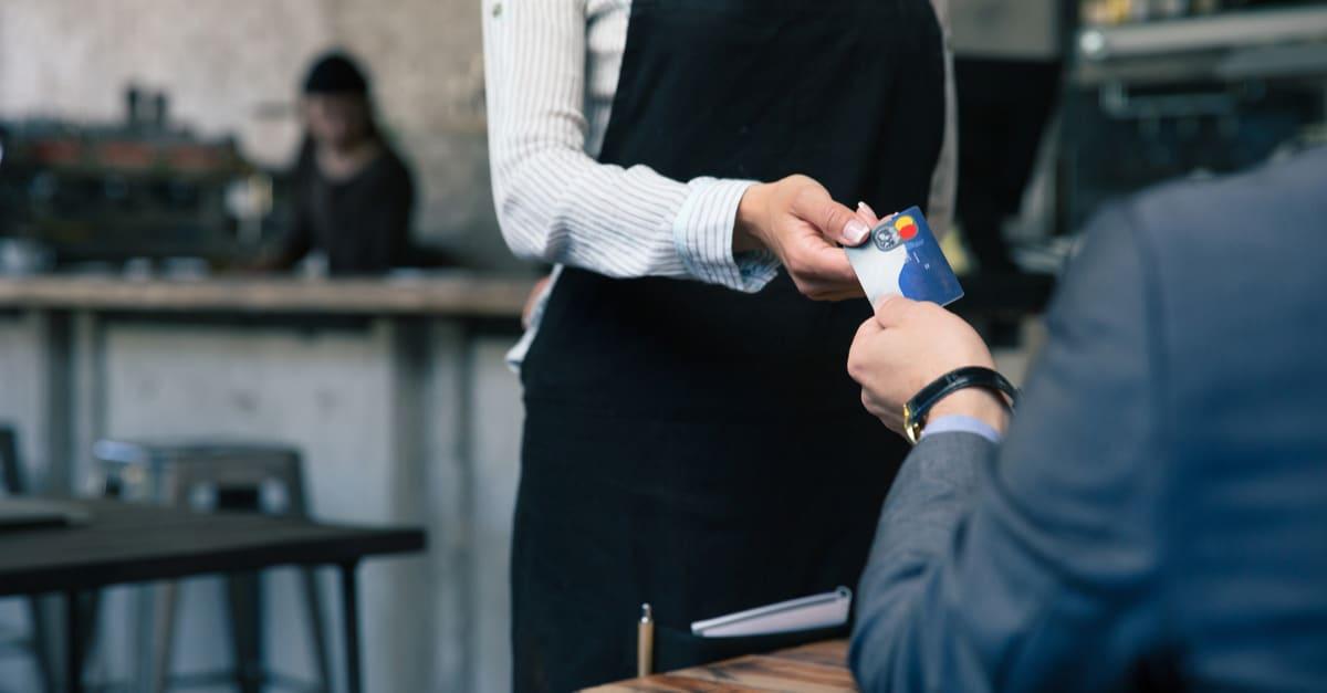 Imagen de cierre de un hombre dando tarjeta de crédito al camarero en el café