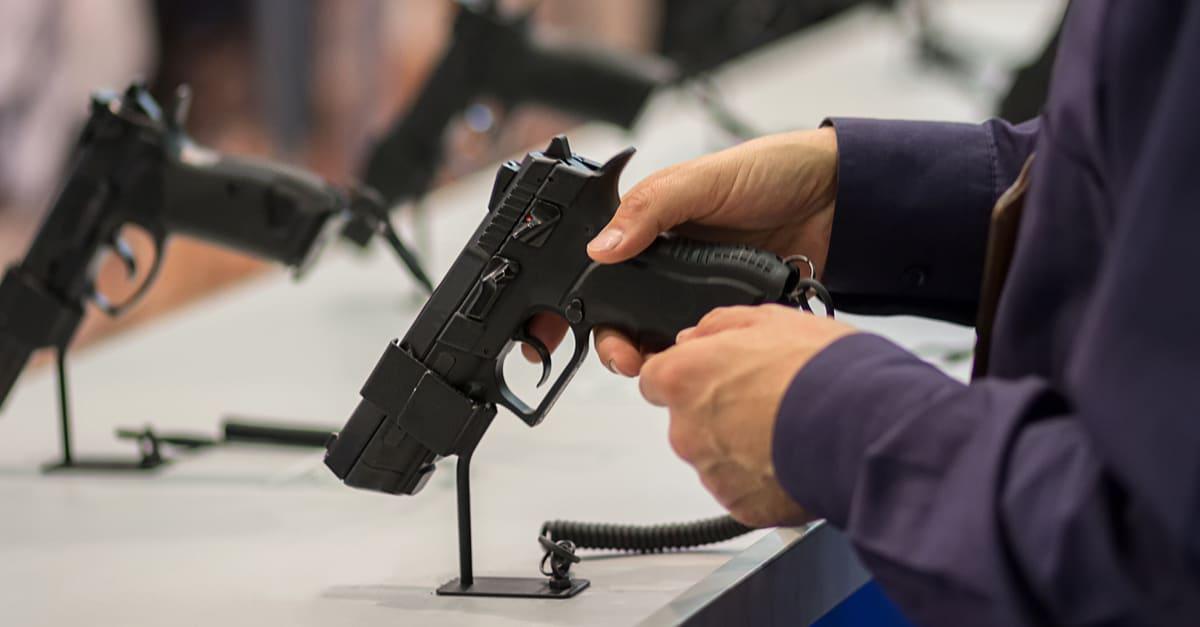 Manos agarrando pistola en una tienda de armas