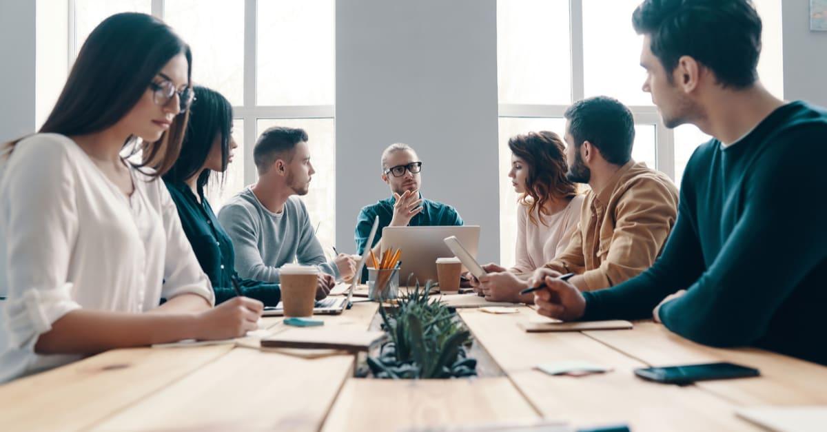 Reunión del personal. Grupo de jóvenes modernos con ropa informal inteligente discutiendo algo mientras trabajan en la oficina creativa trabajos de estados unidos
