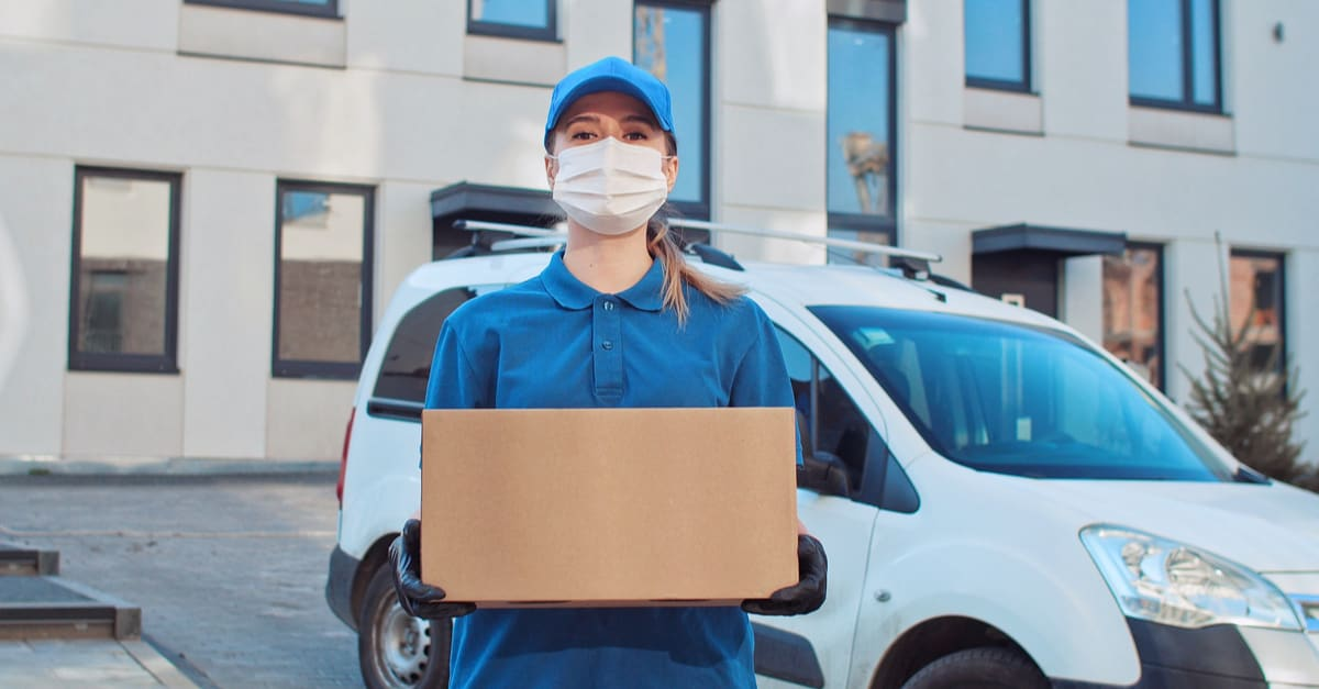 Retrato de una joven trabajadora postal caucásica con guantes y máscaras médicas pisando delante de la cámara con un paquete en las manos.