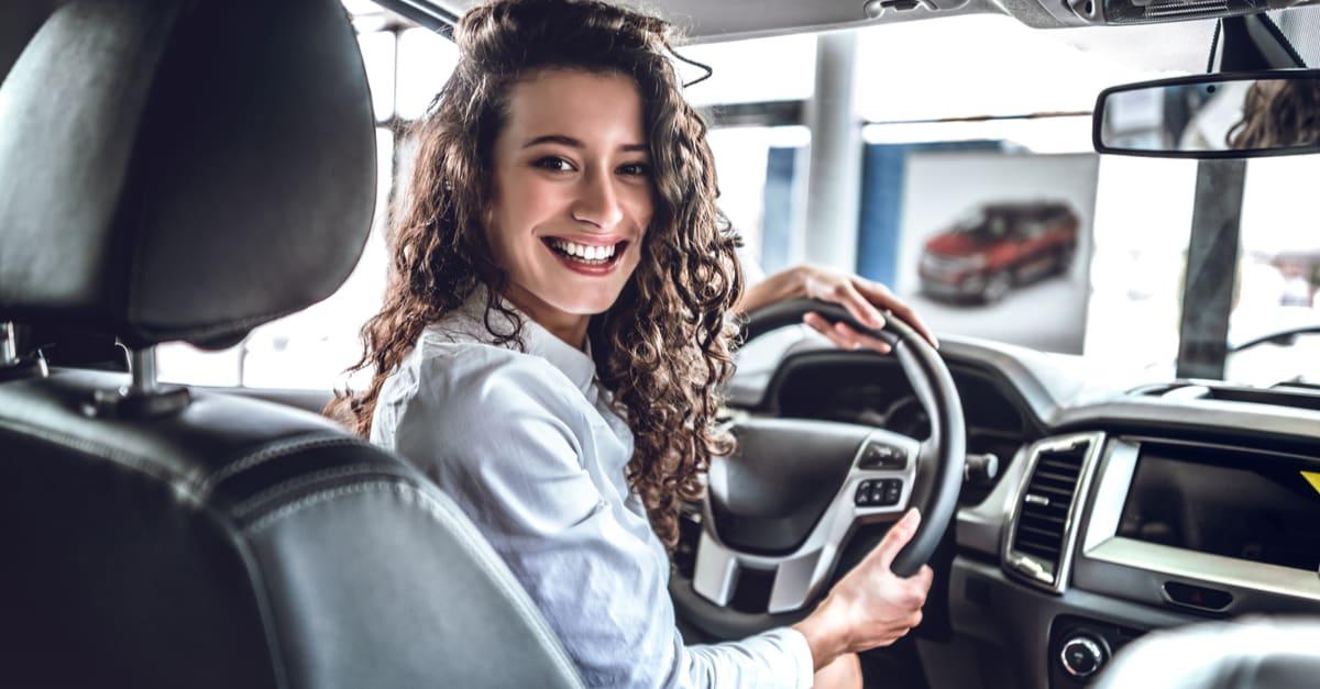 trabajos para mujeres Mujer feliz dentro del camión en auto show o salón.