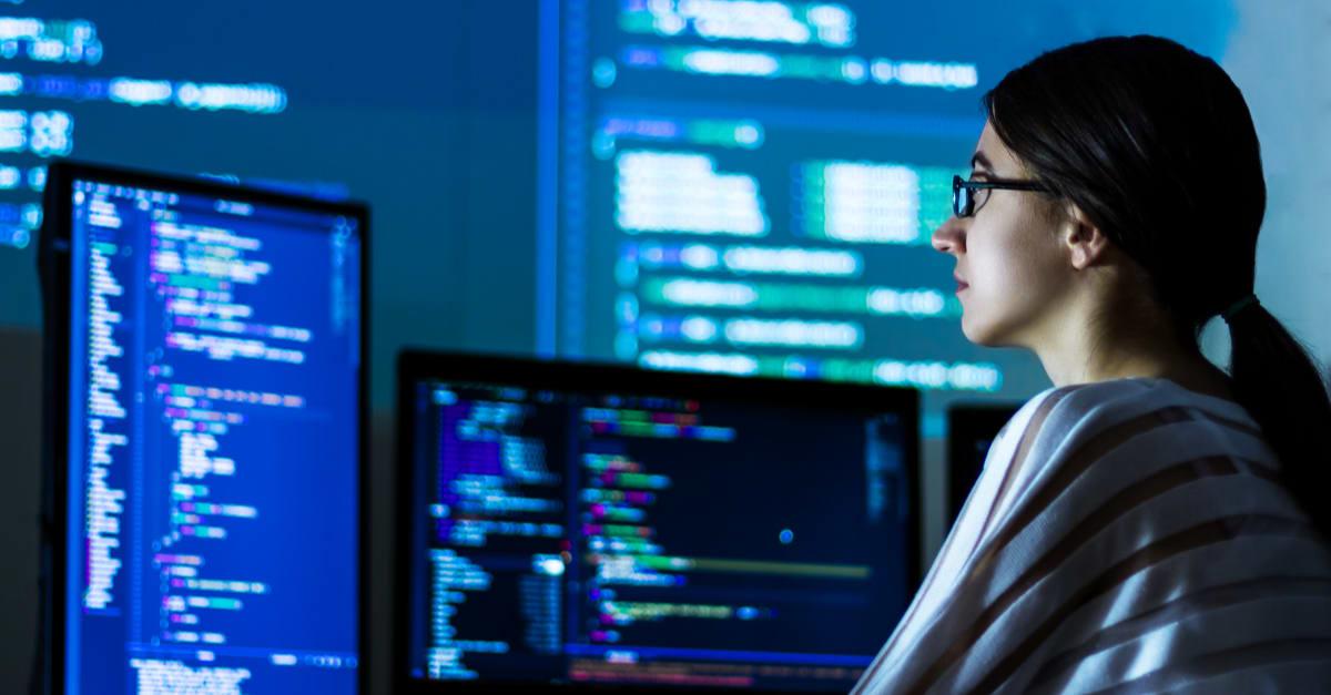 Desarrolladora de software mujer independiente en anteojos trabaja con el código de programa C Java Java Javascript en pantallas anchas durante la noche trabajos de mujeres