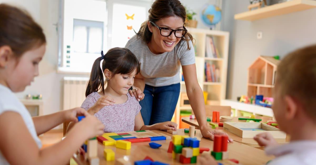 Profesora de preescolar con niños jugando con coloridos juguetes didácticos de madera en el jardín de infantes trabajos para mujeres