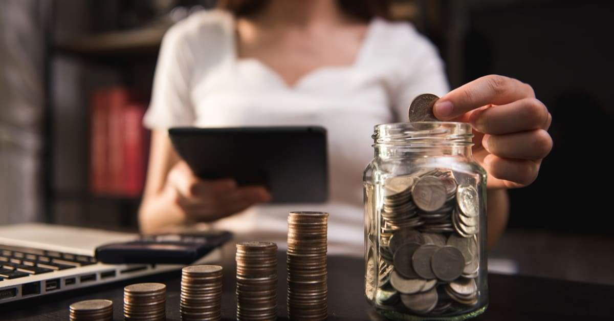 empresario sostiene monedas que se ponen en vidrio con el uso de smartphone y calculadora para calcular el concepto de ahorro de dinero para la contabilidad financiera