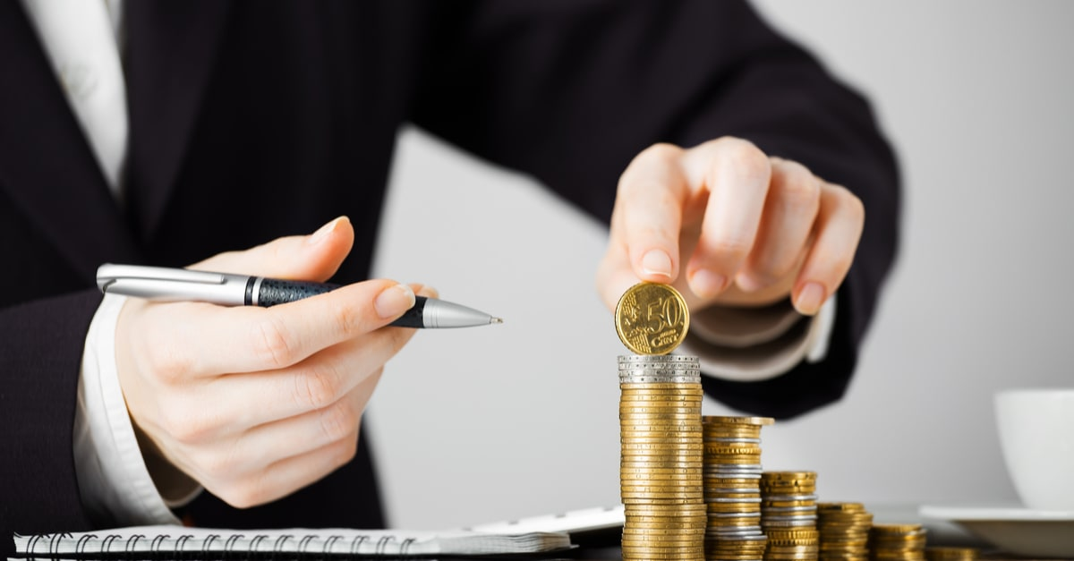 Close-up Of Businesswomans Hands with money coins in office on wooden desk certificados de deposito