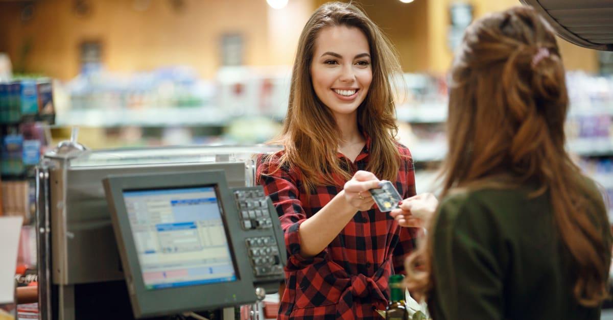 Imagen de una joven sonriente parada en una tienda de supermercados cerca del mostrador