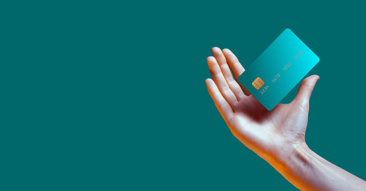 Cerrar mano hembra levanta maqueta de plantilla Tarjeta de crédito bancaria con servicio en línea aislado en fondo verde