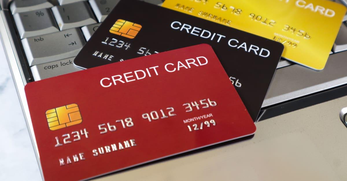 Las tarjeta de crédito se burlan y la tableta de ordenador con fondo de mármol blanco. Concepto de compras en línea