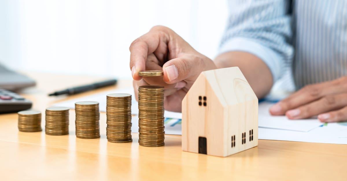 Hombre de negocios asiático incrementando la moneda en monedas apiladas con modelo de casa mientras se prepara para ahorrar para inversión inmobiliaria e hipoteca
