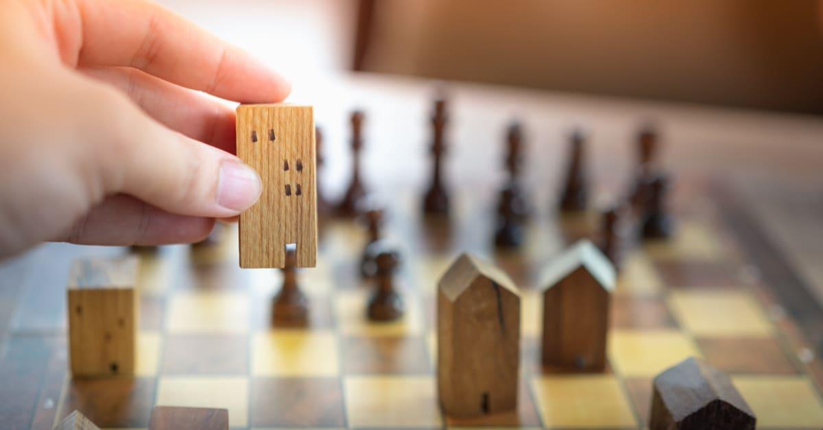 Mano del hombre de negocios que mueve el ajedrez a la construcción y los modelos de casa en el juego de ajedrez, la competencia éxito juego. concepto de estrategia, gestión o liderazgo