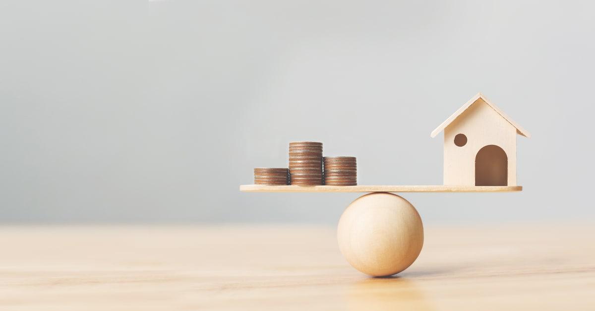 Las monedas de madera de casa y dinero se apilan a escala de madera. Inversión inmobiliaria e hipoteca inmobiliaria financiera concepto