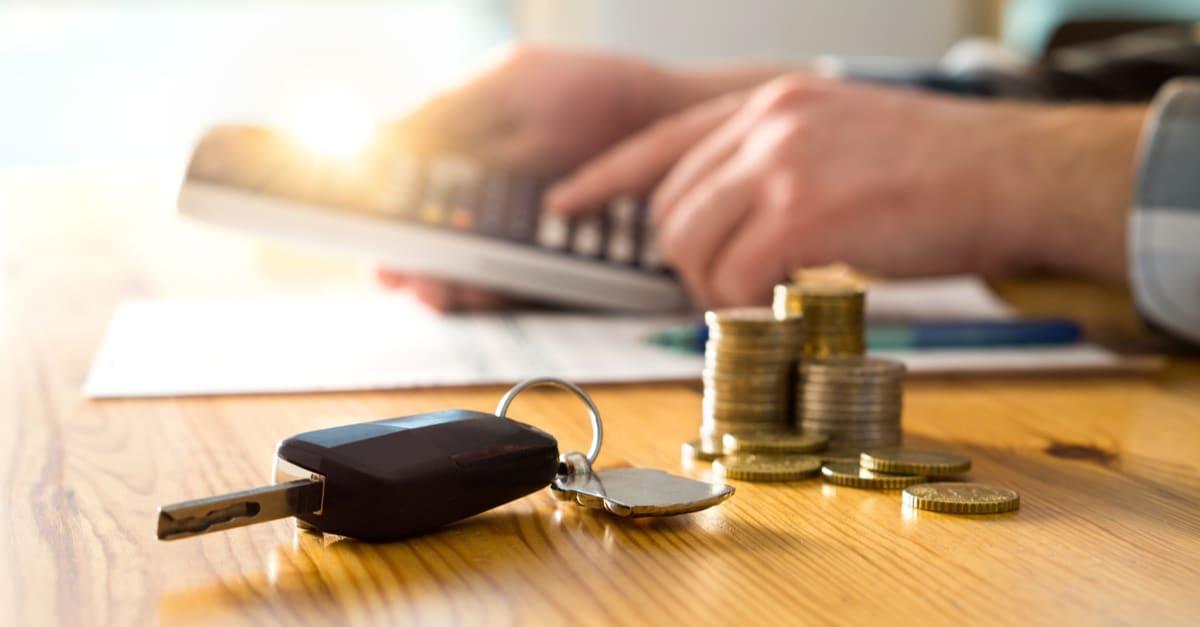 Llaves de Camión y dinero en la mesa con el hombre usando calculadora.