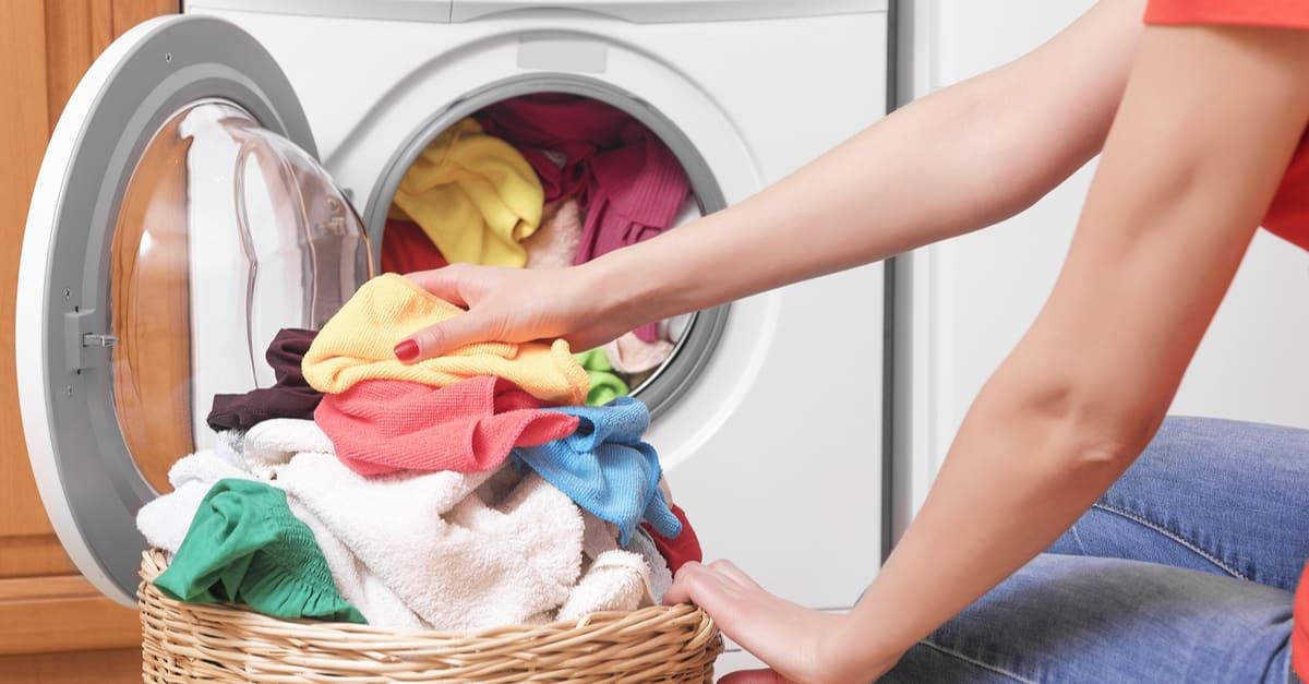 Preparando el ciclo de lavado. Lavadora, manos y ropa.