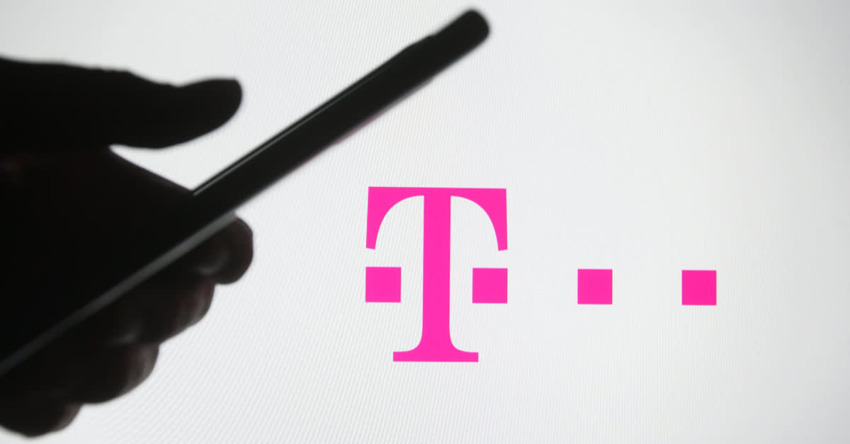 In this photo illustration a silhouette of a hand is seen holding a phone in front of T-mobile logo on a screen