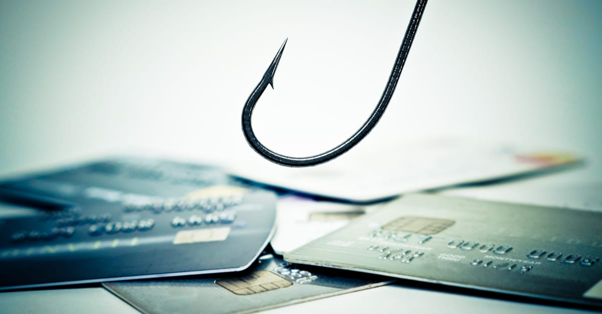 a fish hook over a pile of credit card
