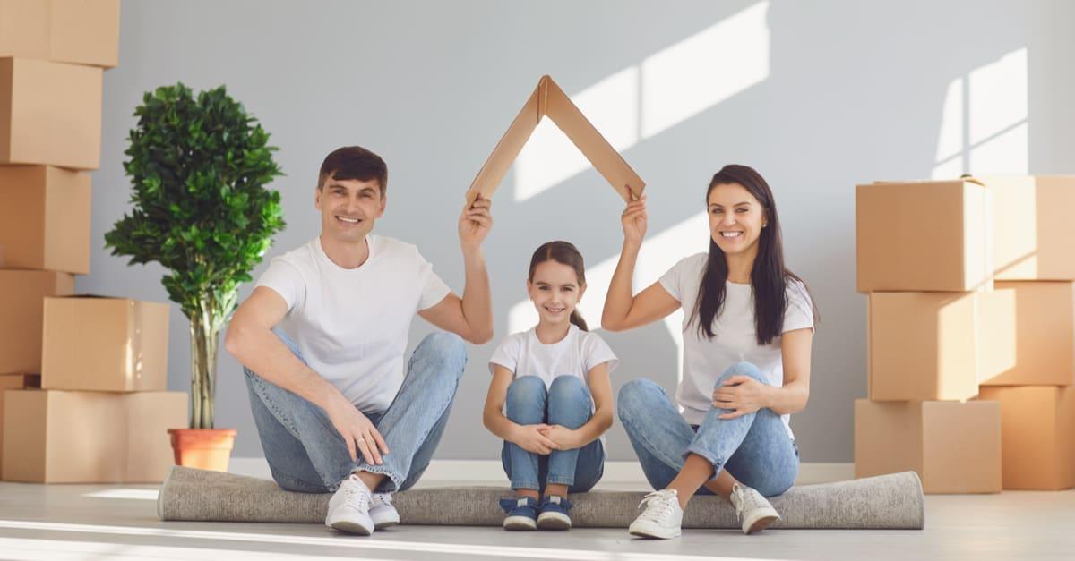 Feliz familia con hijos mudándose en una casa de departamentos nueva