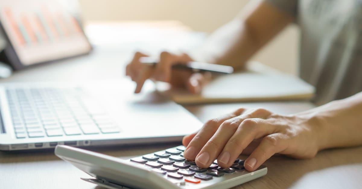 cerrar las manos del contable que calcula la devolución de impuestos usando la calculadora dinero
