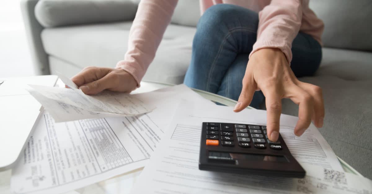 Mano con calculadora haciendo operaciones con intención de mejorar puntaje de crédito