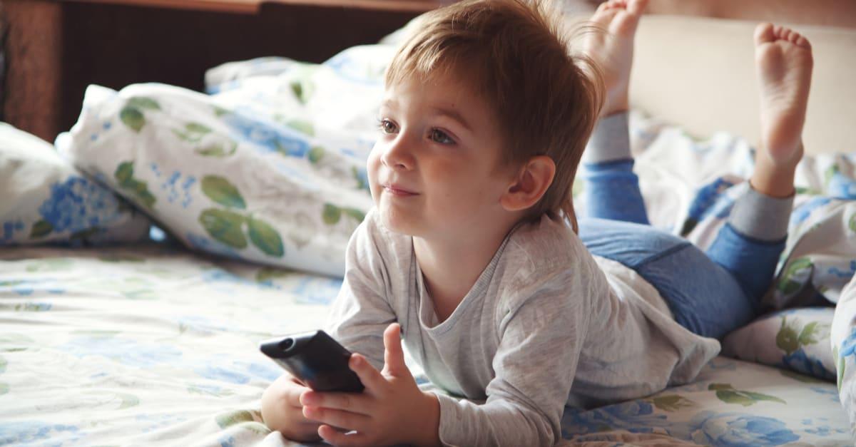 Un niño viendo películas en su cama