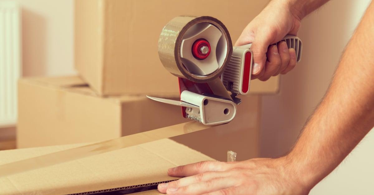 Una persona sellando una caja de mudanza