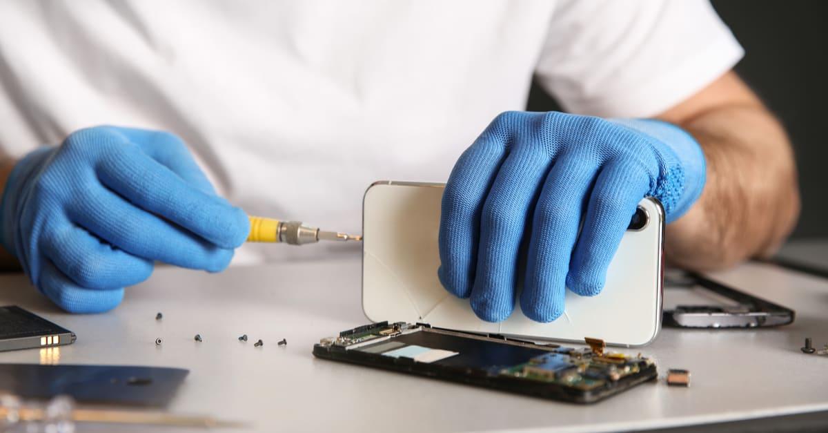 Un técnico trabajando con un teléfono reparado