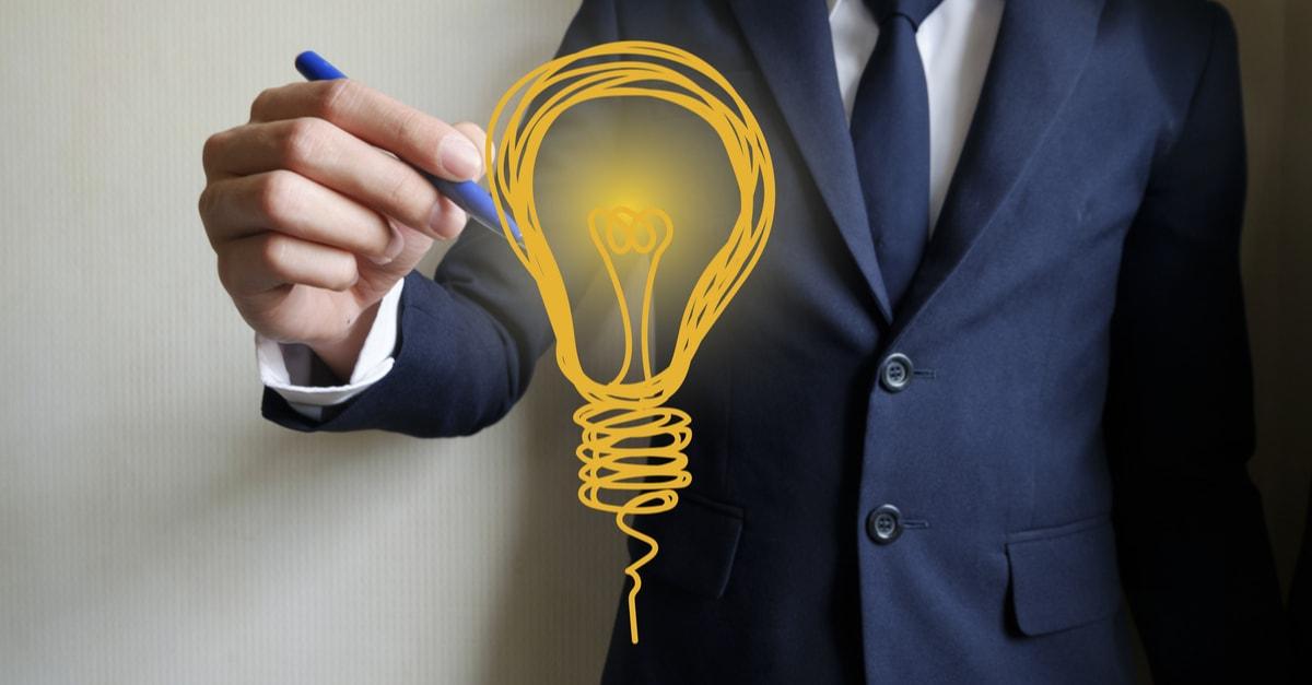 businessman hand writing light bulb