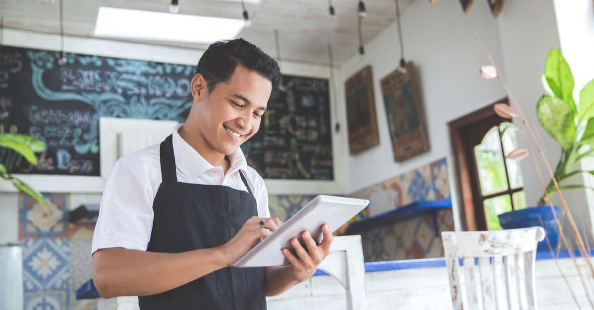 retrato del joven dueño de un café asiático con tableta en nombre