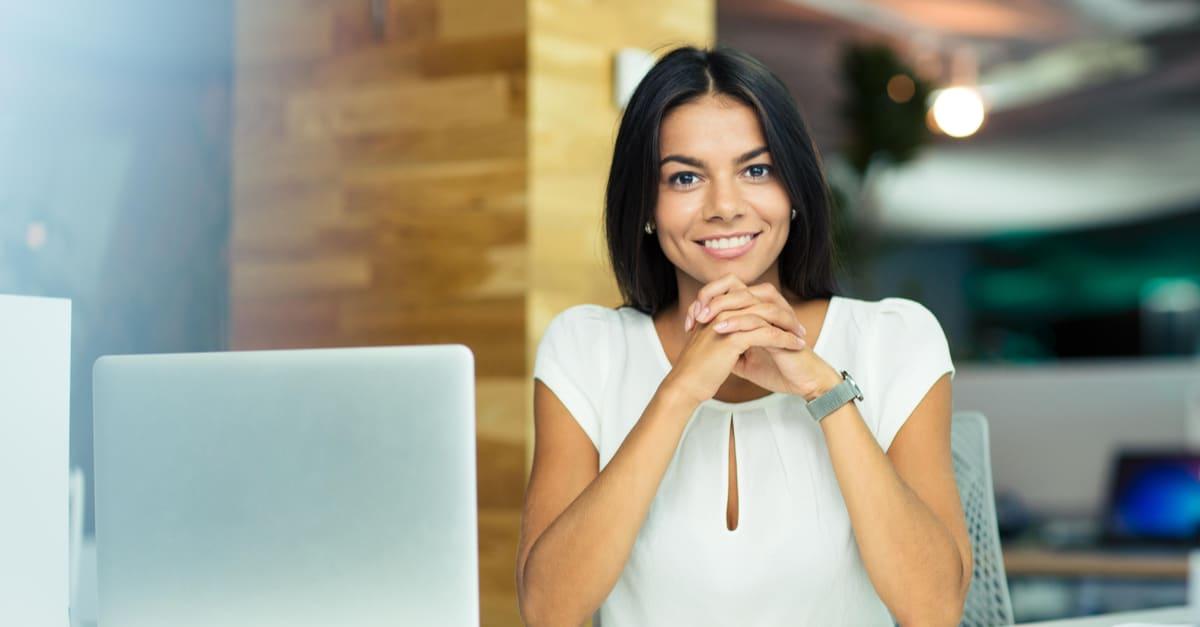 Retrato de una alegre mujer de negocios sentada en la mesa en la oficina y mirando la cámara