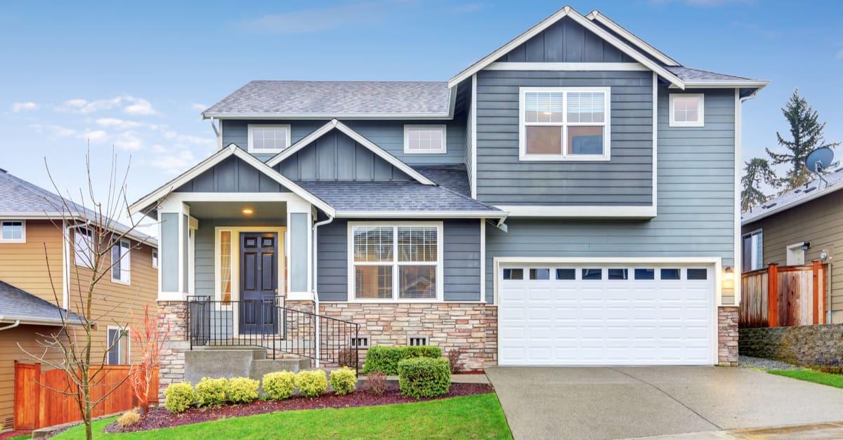 Casa gris exterior con porche de columna en un día lluvioso