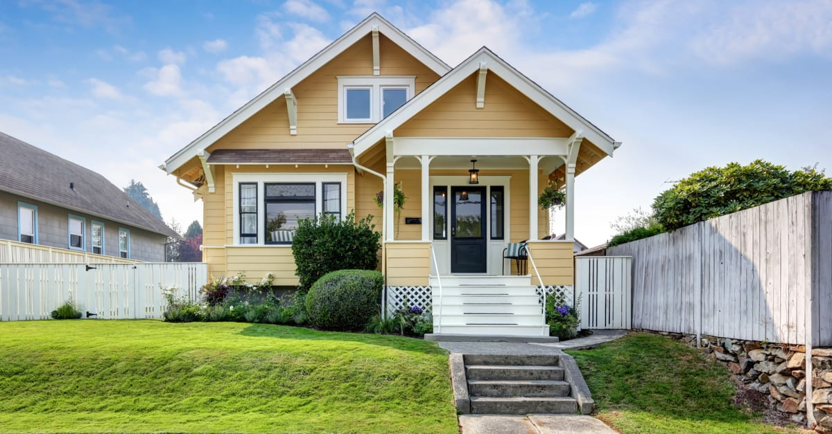 American handcrafted house with yellow exterior paint and manicured front yard