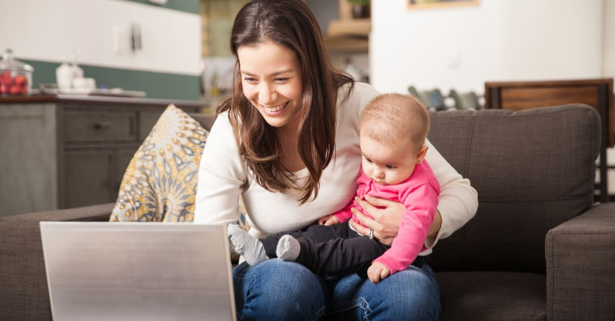 Young woman using laptop to work at home while taking care of her baby