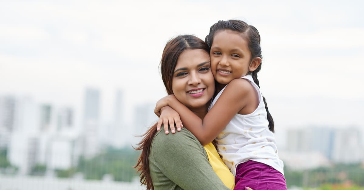Portrait of mother and daughter hugging with smile