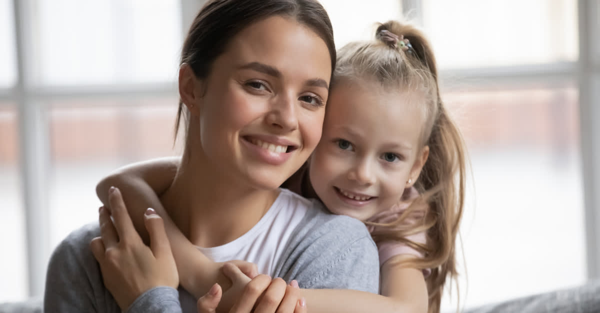 Portrait of a happy mother and little girl hugging on the sofa