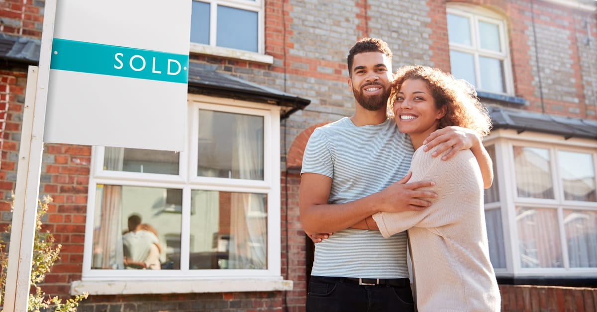 Portrait Of An Excited Couple Outside A New Home With Sold Sign