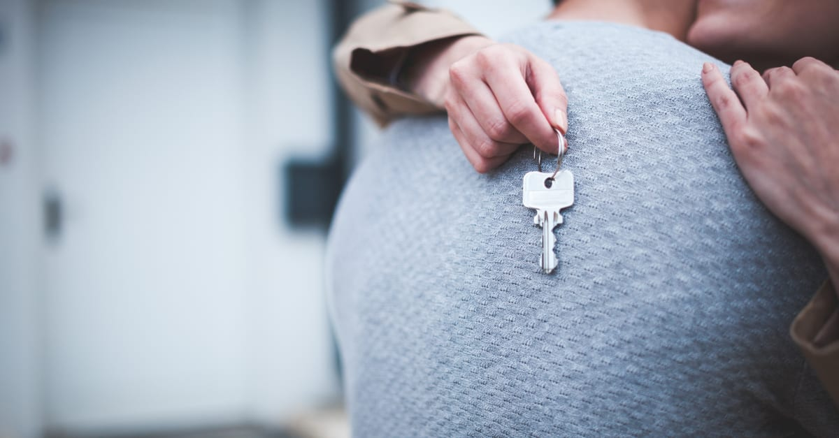 Young woman holding keys hugging her husband in front of their new home after buying real estate