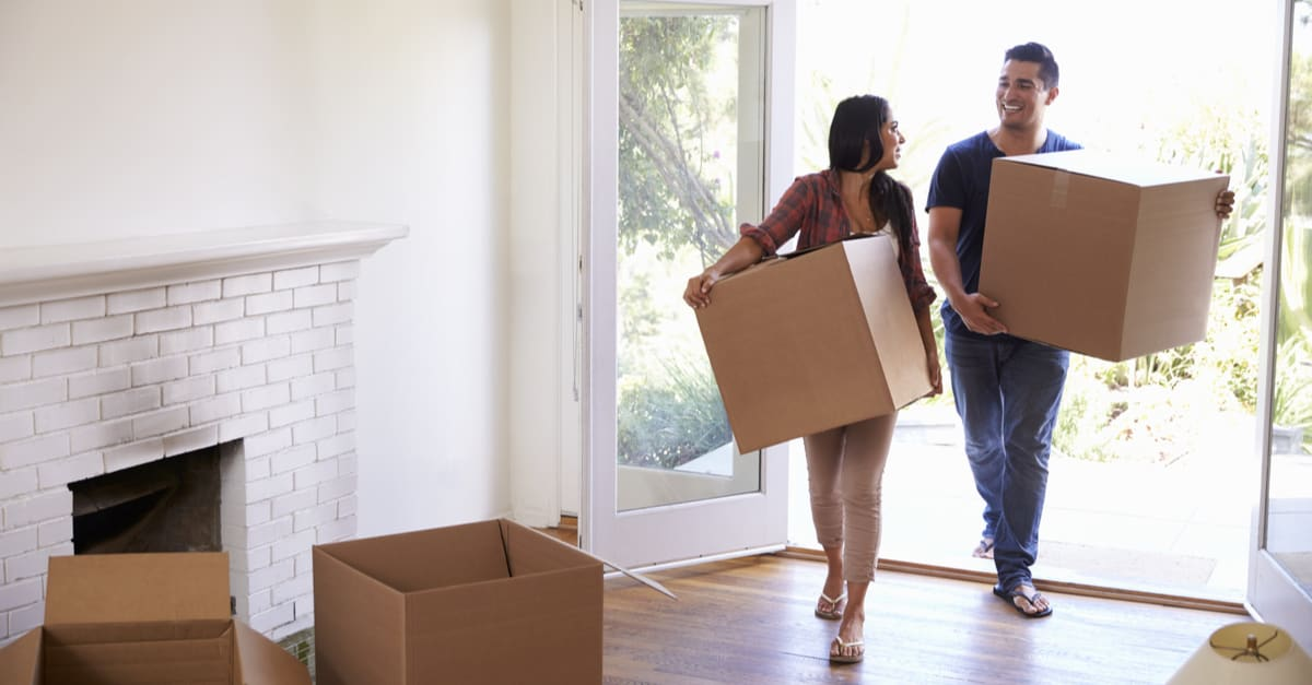 A Couple Carry Boxes Into A New House On Moving Day