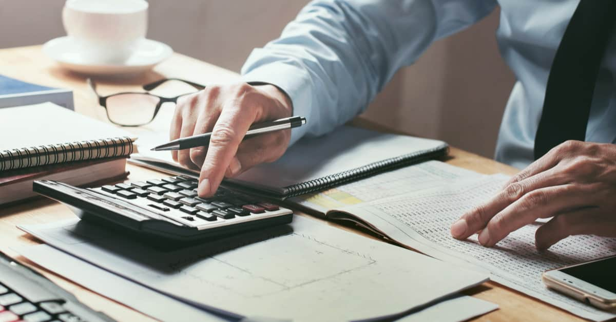 businessman working in a desk office with a calculator to calculate numbers, financial accounting concept